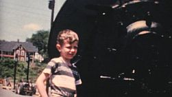 A cute little boy stands beside an old steam train locomotive in the fall of 1959.
