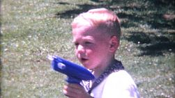 A cute little blond haired boy has fun blowing bubbles from his toy gun in the summer of 1967.