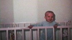A cute little boy plays around in his crib and smiles for the camera.
