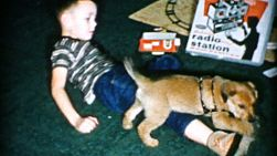 A little boy enjoys playing with his brand new puppy on Christmas morning in 1956.