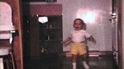 A cute little boy wearing yellow shorts walking around inside his house.