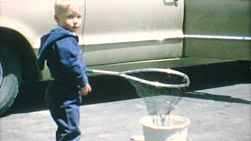 A cute little blond haired boy spends time fishing in his driveway with his new fishing net in the summer of 1967.
