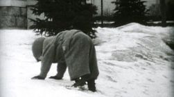 Two cute little boys playing with each other on the ice and snow during the winter of 1955.