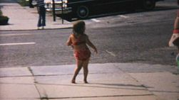A cute little 6 year old girl dances on the sidewalk in her bathing suit on her way to the beach in Florida in 1967.
