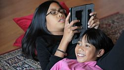 An Asian girls reads a story to her cute 8 year old sister using her new digital tablet.