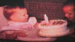 A little girl celebrates her first birthday and sticks her hand in the cake.