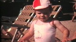 A cute little girl wears her new red bathing suit and hat to the beach.