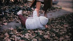 A cute little girl keeps falling on the sidewalk despite the help she receives from her older sisters and mother in the fall of 1961.