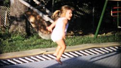 A little girl has fun jumping on an in ground trampoline in the back yard in the summer of 1967.