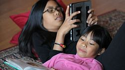 Two cute Asian sisters enjoy spending time together reading a book and playing on a new digital tablet in the living room.