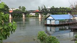 A long-tail boat speeds under the famous Bridge on the River Kwai near Kanchanaburi in Western Thailand.