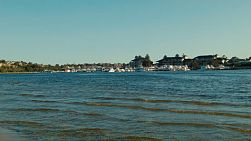 Looking across the Swan River in Perth, Australia, with boats moored at a yacht club in the distance.