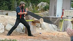 A manly lumberjack competes in the traditional cross cutting saw competition.