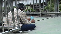 A homeless man shakes a cup while begging on the streets of Bangkok, Thailand wearing a polka dot hat.