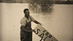 "A man shows his sense of humor by holding up a ""for sale"" sign at his flooded home during the floods of 1948 in Dallas, Texas."