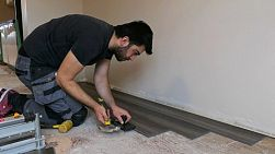 VANCOUVER, BC, CANADA, OCTOBER 15, 2017: A professional installer lays down brand new vinyl plank flooring in a home renovation.