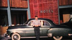 A proud young man shows off his beautiful new car in front of a hotel in 1964.