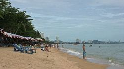 A man talks on his cell phone while dipping his toes in the water at the beach in Pattaya, Thailand.