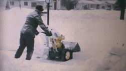A classic Canadiana clip of a man using a snowblower to clear the snow after a winter blizzard hitting hard during the winter of 1970 in Canada.