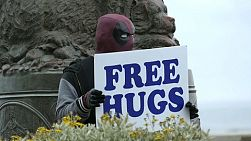 A man wearing a Deadpool mask holds a sign offering free hugs to the public.