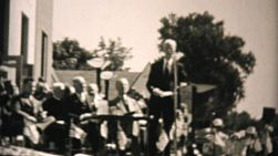 A large audience listens to the town mayor at an important outdoor function in the summer of 1955.