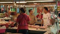 Young men buying meat from a stall at a fresh food market in Bangkok, Thailand.