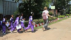 A female young adult overseas missionary takes her class of Asian children on a special outing in Chiang Rai, Thailand.