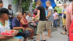 A group of young people on a short-term missions trip hands out 5kg bags of rice to elderly people living in the slums of Bangkok, Thailand.