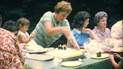 A mom cuts delicious birthday cake for her family at the big summer reunion in 1967.