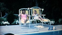 A pretty mother and daughter enjoy spending some time together by the family swimming pool in the summer of 1967.