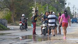 Bangkok, Thailand - April 14, 2014: Various people on motorbikes getting stopped on a road so that they can be splashed with water and powder during the Songkran Festival water fights in Thailand.