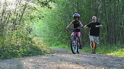 An excited dad helps her young Asian daughter ride her new bike without training wheels for the first time on the pretty forest path.