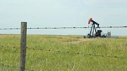 A lonely oil pump works tirelessly behind a barbed wire fence on the barren Canadian prairies.