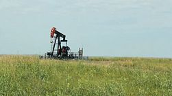 A lonely oil pump works tirelessly on the barren Canadian prairies.