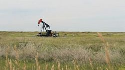 A lonely oil pump works endlessly in the middle of the barren Canadian prairies.