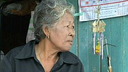 A close up shot of an old Thai lady sitting and talking in a Bangkok, Thailand slum.