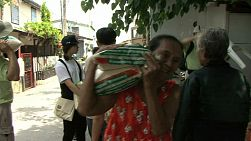 An elderly Thai lady carries a big bag of rice on her shoulder in a slum in Bangkok, Thailand.