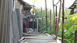An old Thai lady leaves her shack with a friend to go out looking for work in the slums of Bangkok, Thailand.