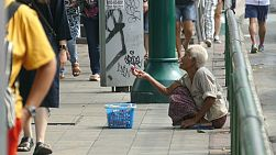 An elderly Thai woman desperately tries to sell her items for money on the streets of Bangkok, Thailand.