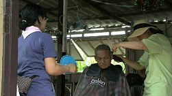 An old Thai man gets a hair cut at a salon in the slums of Bangkok, Thailand.