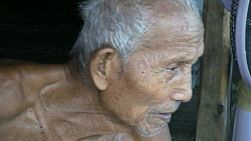 A close up shot of an old Thai man who is suffering from the heat in the slums of Bangkok, Thailand.