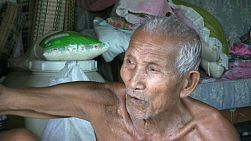 A close up shot of an old Thai man talking about the good old days in the slums of Bangkok, Thailand.