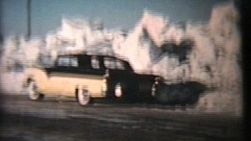 A black and yellow vintage 57 Ford is parked in front of massive snow banks after a winter blizzard in the prairies.