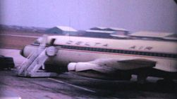 People boarding an old Delta commercial airplane from the tarmac in the summer of 1964.