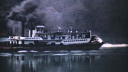 An old paddlewheel barge takes a load up a river in Ohio in the 1940s.