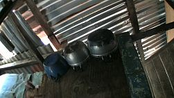 A funky tilt down shot of old pots and lids inside a typical slum home in Bangkok, Thailand.