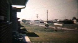 An Old Truck Passing By On A Suburban Road. (Vintage 8mm film footage from 1960)