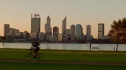 Various people passing by as they cycle and walk along the South Perth Foreshore, with a view of the Swan River and city skyline in the background.
