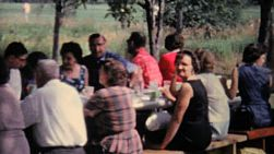 People enjoying a delicious meal at a large family picnic in the summer of 1962.