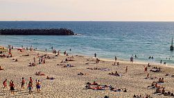Lots of people swimming, relaxing and sunbathing at Cottesloe Beach in Western Australia, on a hot day in spring.